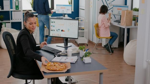 Zakenvrouw op lunchpauze aan haar tafel eten pizza fastfood levering