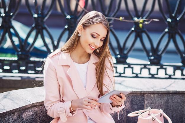 Zakenvrouw op pauze in het park. jonge professionele bedrijfsvrouw die tabletcomputer met behulp van openlucht. kaukasisch vrouwelijk model.