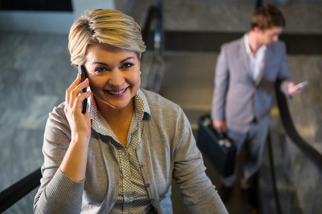 Zakenvrouw op roltrap praten op mobiele telefoon