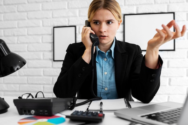 Zakenvrouw op zoek geïrriteerd tijdens het gesprek aan de telefoon