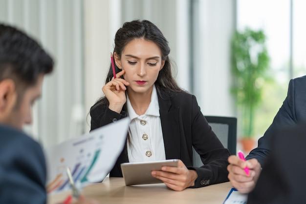 Zakenvrouw op zoek plan van marketing op tablet tijdens een ontmoeting met collega's op kantoor