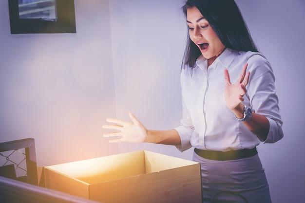 Zakenvrouw opent kartonnen doos met verrassing emotie voor iets binnen