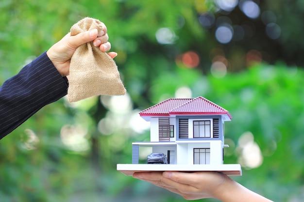 Zakenvrouw overhandigde het geld in zak aan vrouw met model huis en auto, nieuw huis en onroerend goed handel concepten