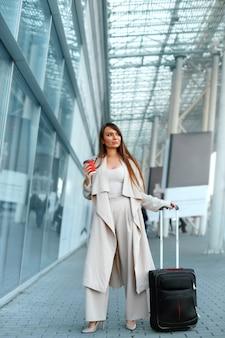 Zakenvrouw permanent in de buurt van de luchthaven met bagage tijdens de zakenreis Premium Foto