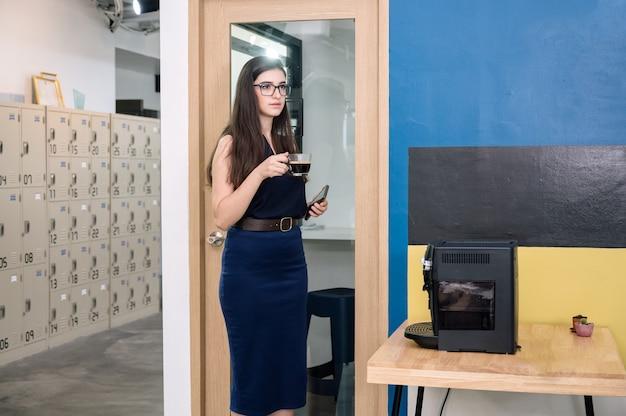 Zakenvrouw permanent met hete koffie drinken op kantoor