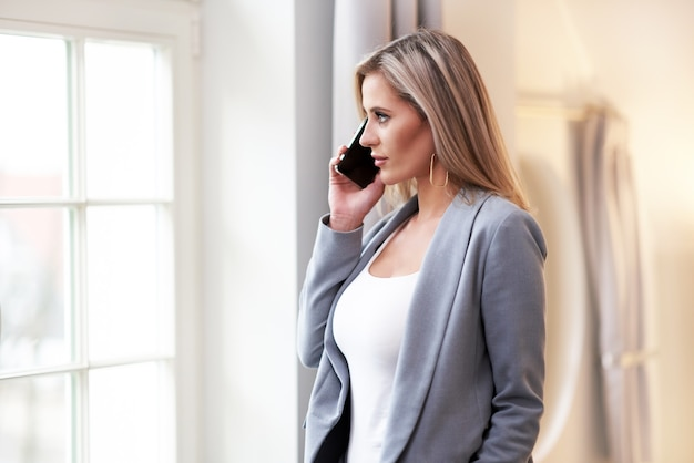 Zakenvrouw praten aan de telefoon in hotelkamer