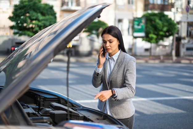Zakenvrouw praten aan de telefoon terwijl haar auto het begaf