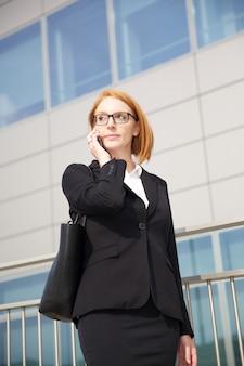Zakenvrouw praten met mobiel in stedelijke omgeving