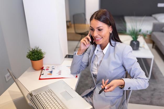 Zakenvrouw praten op haar mobiele telefoon tijdens het werken vanuit huis