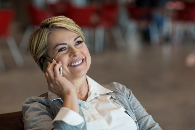 Zakenvrouw praten op mobiele telefoon in wachtruimte