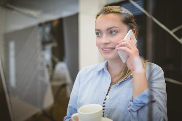 Zakenvrouw praten over de telefoon tijdens de koffiepauze