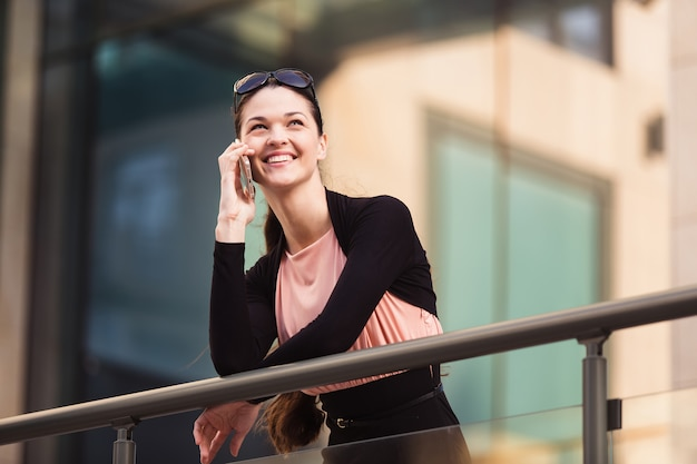 Zakenvrouw praten over de telefoon tijdens een koffiepauze buiten het kantoor