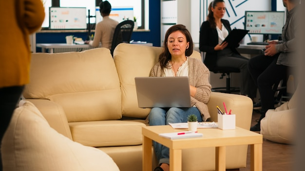 Zakenvrouw praten tijdens videoconferentie bellen vanaf laptop zittend op de bank. manager executive communiceert in online virtuele chat-vergadering op afstand, kijkend naar pc die werkt vanuit een modern kantoor.