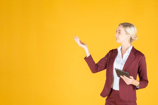Zakenvrouw presenteert iets op gele achtergrond