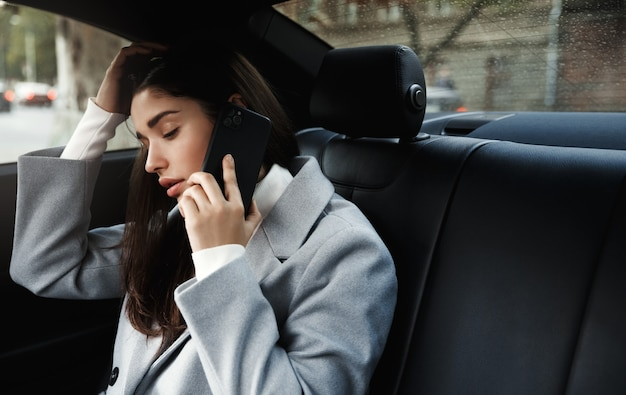 Zakenvrouw reizen naar kantoor in een auto zittend op de achterbank en praten over mobiel