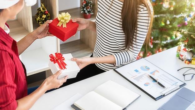 Zakenvrouw ruilen een cadeau in kantoor op de laatste werkdag. jonge creatieve mensen vieren vakantie in een modern kantoor.