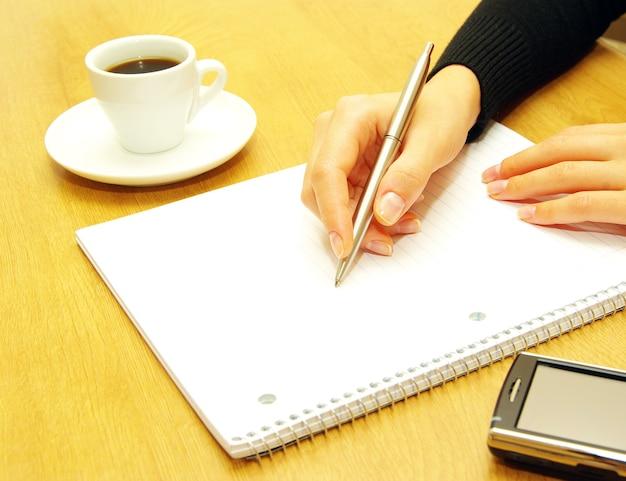 Zakenvrouw schrijft een pen op een leeg papier