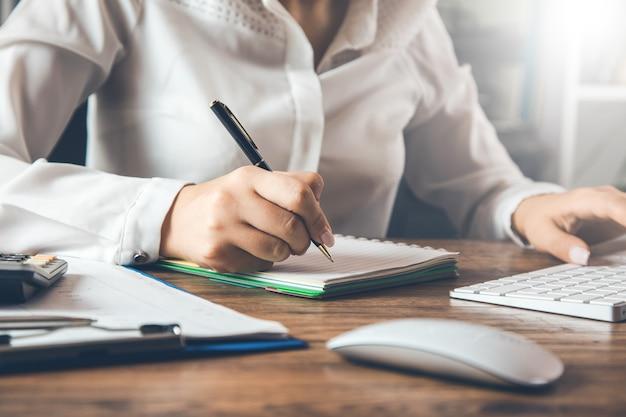 Zakenvrouw schrijven met pen in kladblok