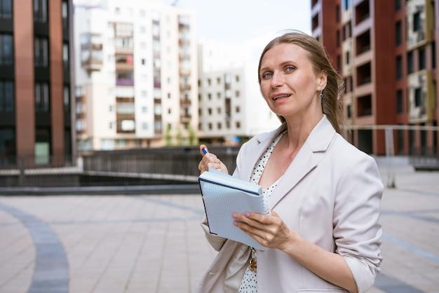 Zakenvrouw schrijven met pen in notebook kaukasisch succesvol meisje in lichte jas staat in de buurt van een...