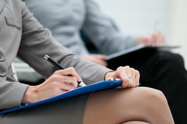 Zakenvrouw schrijven op kladblok tijdens een vergadering, close-up