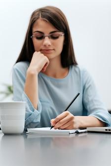 Zakenvrouw schrijven op papier in het kantoor, het schrijven van documenten.