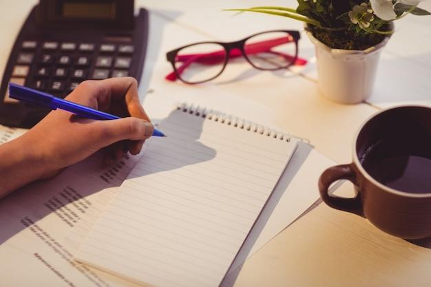 Zakenvrouw schrijven van notities in boek