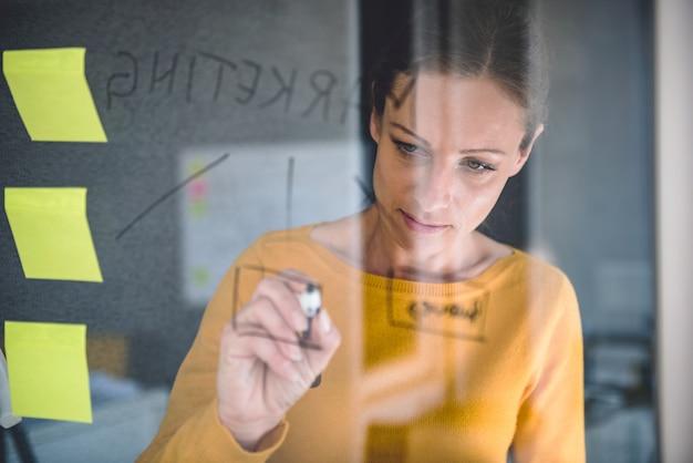 Zakenvrouw schrijven van notities op het bord van glas