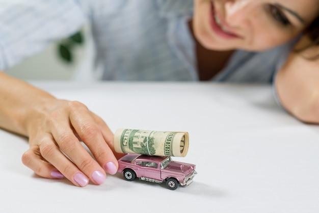 Zakenvrouw speelgoedauto en geld - gericht op succes en geluk
