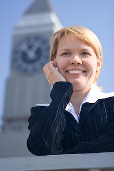Zakenvrouw spreekt telefonisch op straat op een achtergrond van een uurtoren