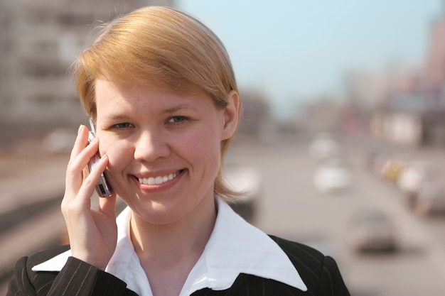 Zakenvrouw spreekt telefonisch op straat