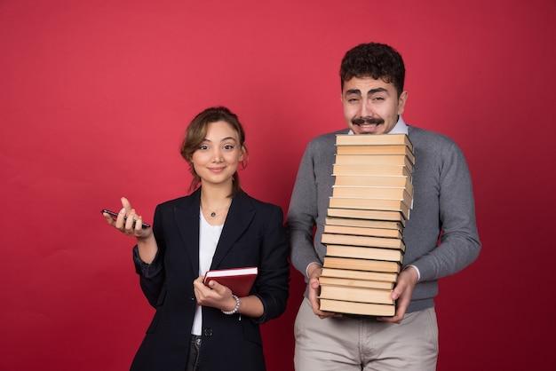 Zakenvrouw staande in de buurt van brunette man met stapel boeken