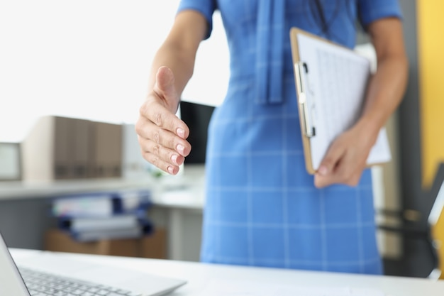 Zakenvrouw strekt hand uit voor handdruk zakelijke regeling concept