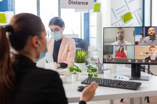 Zakenvrouw tijdens het verwijderen van videoconferentie op computer met gezichtsmasker als veiligheidsmaatregel tijdens wereldwijde pandemie met covid19-griep op nieuwe normale werkplek. online web internet virtueel videogesprek