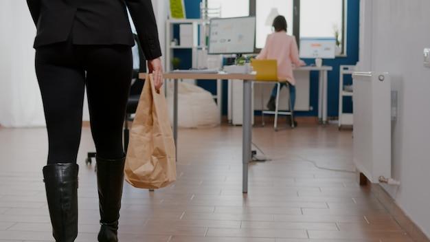Zakenvrouw tijdens lunchpauze die voedselbestelling ontvangt en smakelijk maaltijdpakket op tafel zet tijdens afhaallunch in bedrijfskantoor