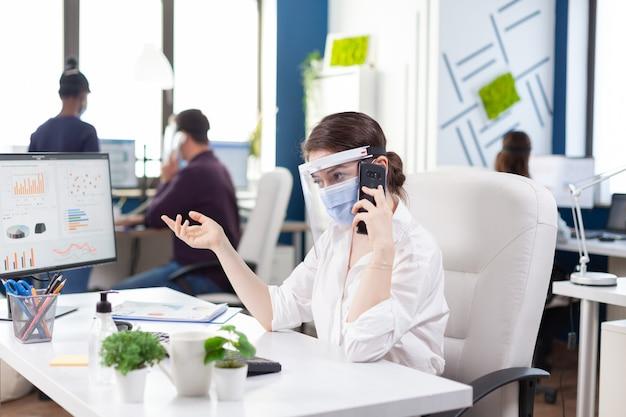 Zakenvrouw tijdens wereldwijde pandemie met covid 19 die een zakelijk gesprek voert met een smartphone met een gezichtsmasker. multi-etnische collega's die werken met respect voor sociale afstand in een financieel bedrijf.