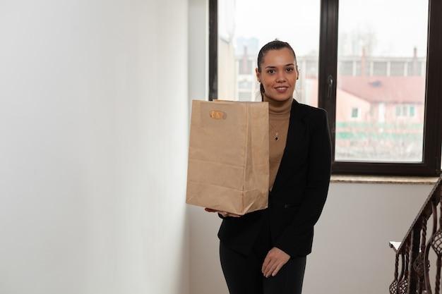Zakenvrouw traplopen in opstarten bedrijf kantoor hoding afhaalmaaltijden maaltijdzak tijdens afhaalmaaltijden. bezorger die een fastfood-lunchbestellingspakket levert aan de manager van de klant