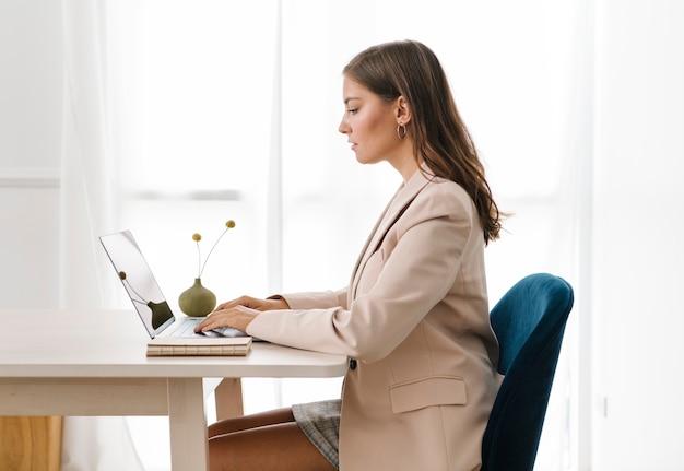 Zakenvrouw typen op haar laptop op een houten tafel