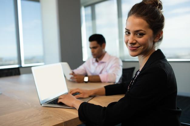 Zakenvrouw typen op laptop aan tafel met mannelijke collega op achtergrond