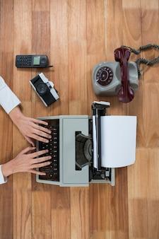 Zakenvrouw typen op typemachine met vintage camera, telefoon en mobiele telefoon