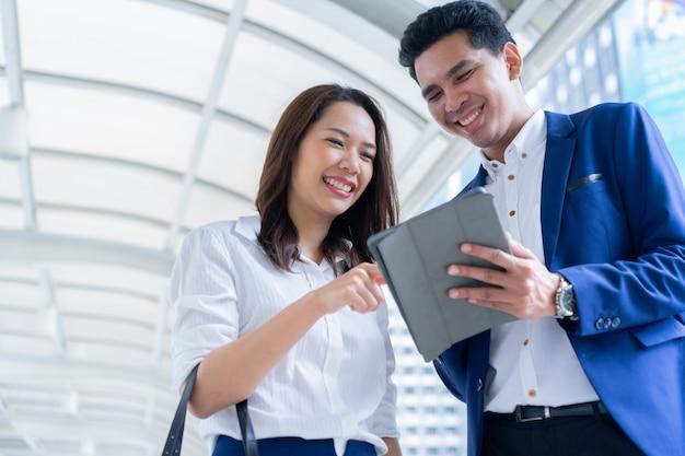 Zakenvrouw uitleggen en kort detail van de marketing van het bedrijf aan zakenman