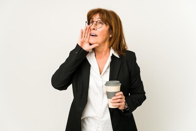 Zakenvrouw van middelbare leeftijd die een afhaalkoffie geïsoleerd houden die en palm dichtbij geopende mond houdt.