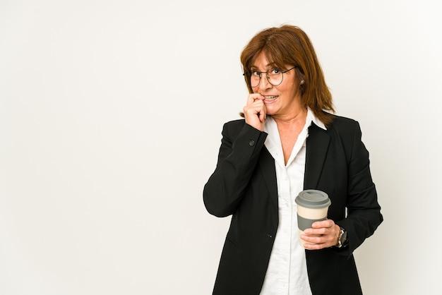 Zakenvrouw van middelbare leeftijd die een afhaalkoffie geïsoleerd houden ontspannen denken aan iets kijken naar een kopie ruimte.