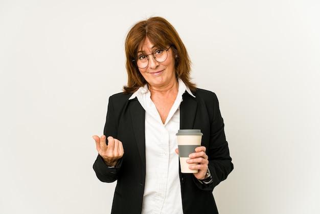 Zakenvrouw van middelbare leeftijd die een afhaalkoffie houdt die met de vinger naar je wijst alsof het uitnodigen dichterbij komt.
