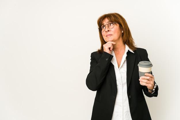 Zakenvrouw van middelbare leeftijd die een afhaalkoffie houdt die zijdelings met twijfelachtige en sceptische uitdrukking kijkt.