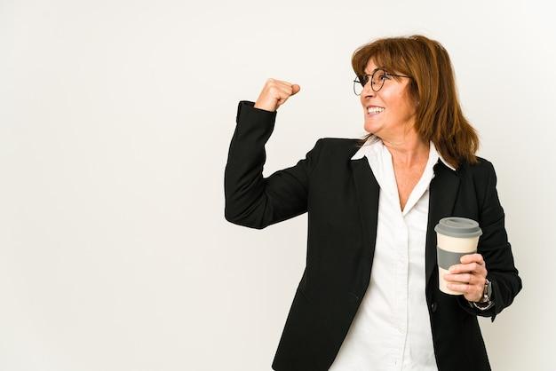 Zakenvrouw van middelbare leeftijd die een afhaalmaaltijdenkoffie geïsoleerd houden die vuist opheft na een overwinning, winnaarconcept.