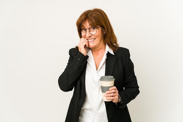 Zakenvrouw van middelbare leeftijd die een afhaalmaaltijdenkoffie houdt die vingernagels bijt, nerveus en zeer angstig.