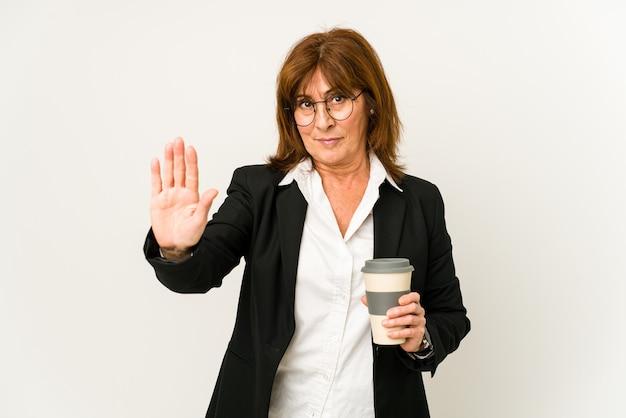 Zakenvrouw van middelbare leeftijd die een afhaalmaaltijdenkoffie houdt geïsoleerd status met uitgestrekte hand die stopbord toont, dat u verhindert.