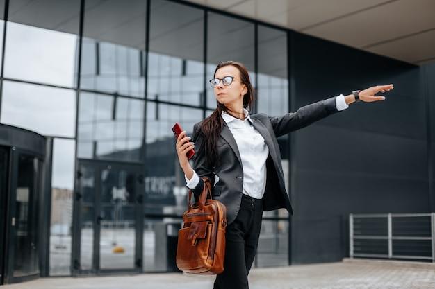 Zakenvrouw vangt een taxi. een vrouw wacht op een auto en gaat naar een zakelijke bijeenkomst. bedrijfsconcept. meisje met bril in de stad in de buurt van het werk.