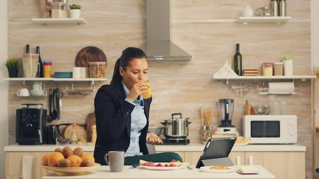 Zakenvrouw vers sap drinken tijdens het ontbijt voor het werk kijken naar een video op tablet. zakenvrouw die het laatste nieuws online leest voordat ze naar haar werk gaat, met behulp van moderne technologie in de keuken die
