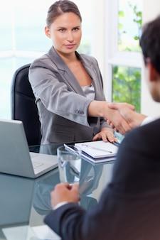 Zakenvrouw verwelkomt klant in haar kantoor